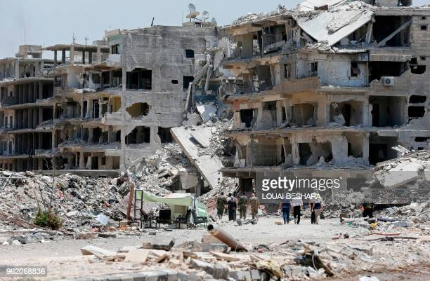 Syrian progovernment forces and civilians walk down a destroyed street following a flag raising ceremony at the entrance of the Hajar alAswad...