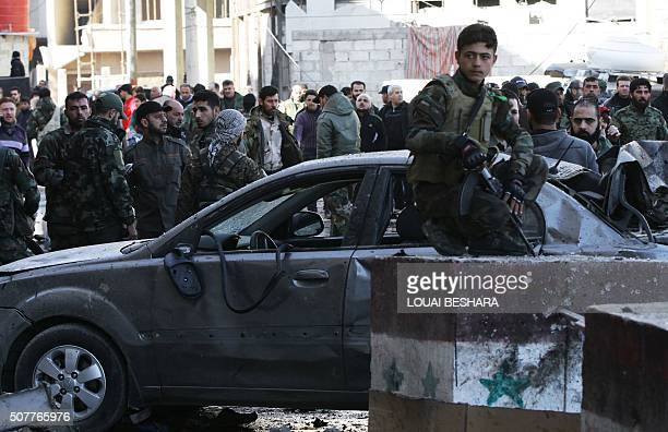 Syrian progovernment forces and residents gather at the site of suicide bombings in the area of a revered Shiite shrine in the town of Sayyida Zeinab...