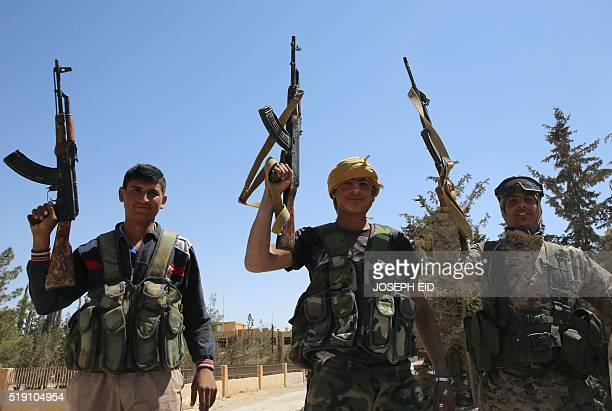 Syrian progovernment forces celebrate on April 4 2016 in alQaryatain a town in the province of Homs in central Syria after Syrian troops regained...