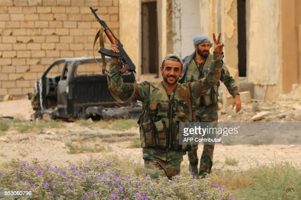 Syrian progovernment forces flash the Vsign from the side of a road on the outskirts of Deir Ezzor on September 24 as government forces continue to...