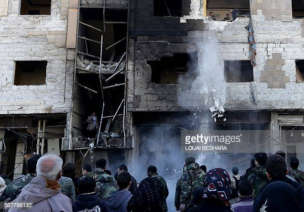 Syrian progovernment forces inspect the damage following suicide bombings in the area of a revered Shiite shrine in the town of Sayyida Zeinab on the...