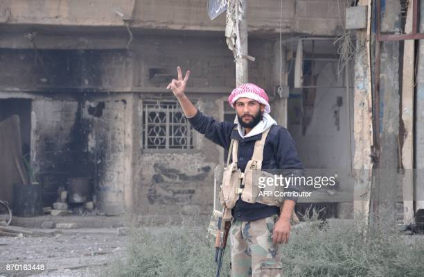 A Syrian progovernment forces member flashes the sign for victory as he patrols in the eastern city of Deir Ezzor on November 4 2017 Syrian and...