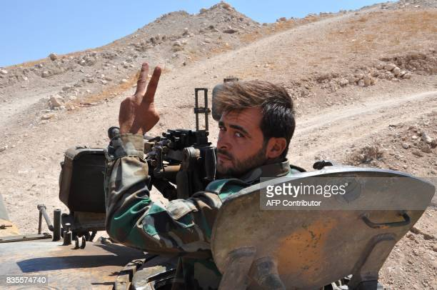 A Syrian progovernment forces member gestures to the camera from a tank in the Salamiyah city some 33 kilometres southeast of Hama on August 19...