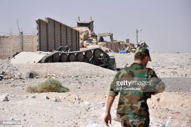 A Syrian progovernment forces member walks past an upsidedown tank in the Jamiyet alRuwad neighbourhood on the northern outskirts of Deir Ezzor on...