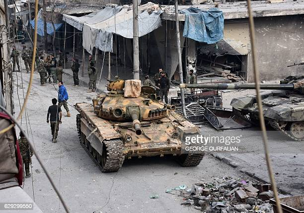 Syrian progovernment forces patrol Aleppo's eastern alSalihin neighbourhood on December 12 2016 after troops retook the area from rebel fighters /...