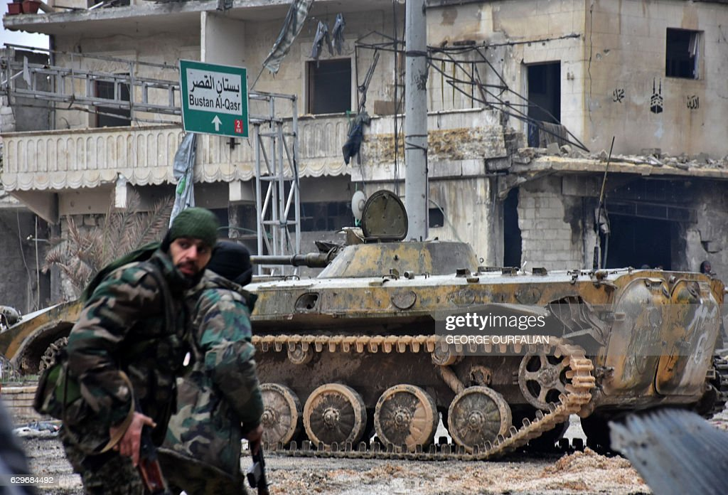 TOPSHOT - Syrian pro-government forces patrol the northern embattled city of Aleppo on December 14, 2016. Shelling and air strikes sent terrified residents running through the streets of Aleppo as a deal to evacuate rebel districts of the city was in danger of falling apart. / AFP / George OURFALIAN