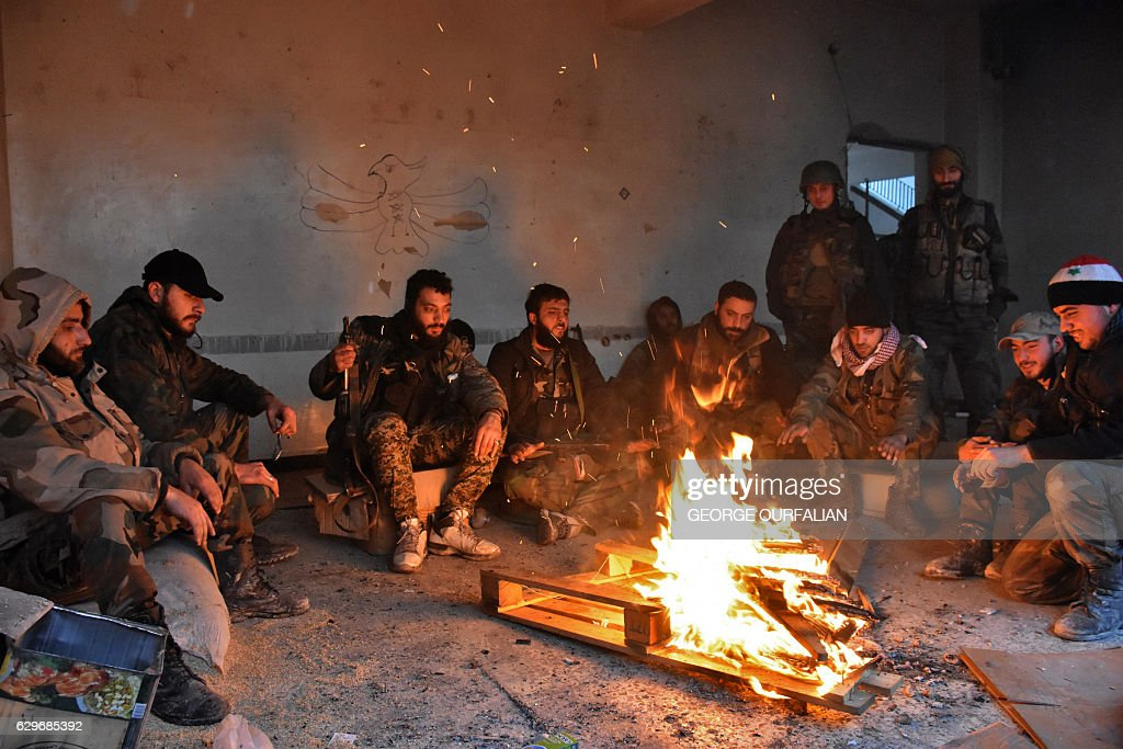 TOPSHOT - Syrian pro-government forces rest by a fire as they advance in the Jisr al-Haj neighbourhood during the ongoing military operation to retake remaining rebel-held areas in the northern embattled city of Aleppo on December 14, 2016. Shelling and air strikes sent terrified residents running through the streets of Aleppo as a deal to evacuate rebel districts of the city was in danger of falling apart. / AFP / George OURFALIAN