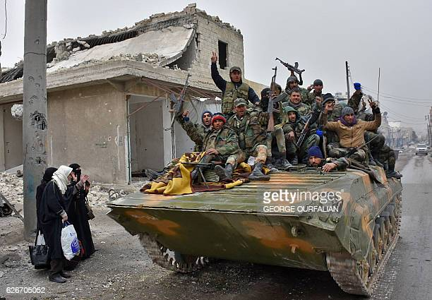 TOPSHOT Syrian progovernment forces sit on a military vehicle driving past residents fleeing the eastern part of Aleppo and gathering in Masaken...