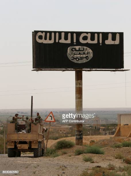 Syrian progovernment forces stand in the back of a truck next to billboard bearing the logo of the Islamic State group in Madan area in the...