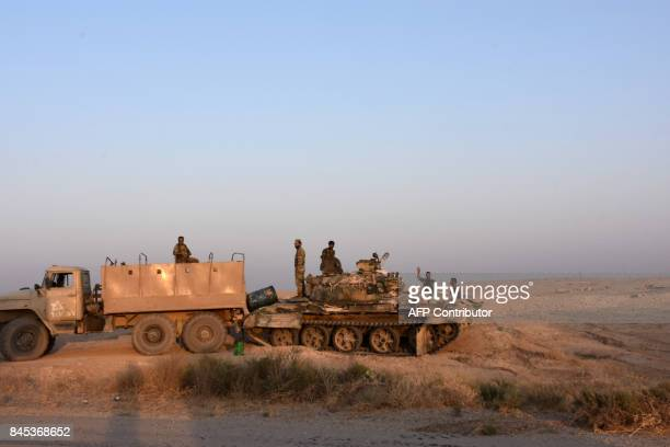 Syrian progovernment forces stand on a tank on the outskirts of the eastern city of Deir Ezzor on September 10 as they continue to press forward with...