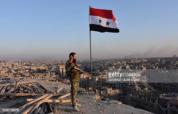 TOPSHOT Syrian progovernment forces stand on top of a building overlooking Aleppo in the city's Bustan alBasha neighbourhood on November 28 during...