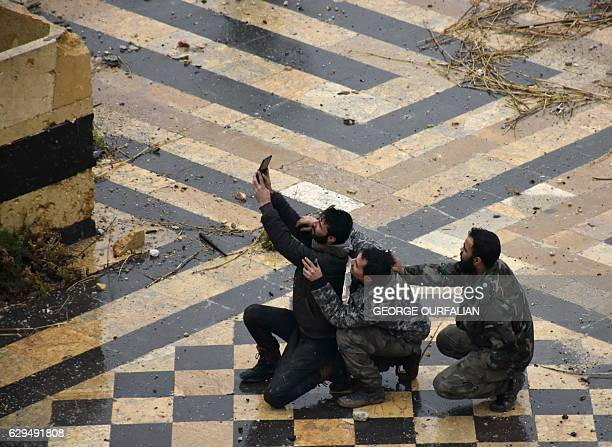 TOPSHOT Syrian progovernment forces take a selfie in the courtyard of the ancient Umayyad mosque in the old city of Aleppo on December 13 2016 After...