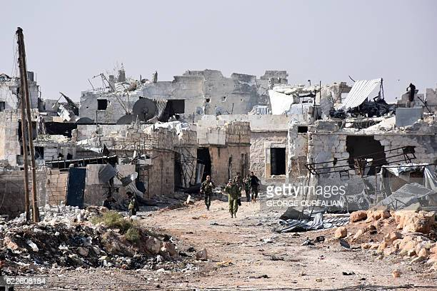 TOPSHOT Syrian progovernment forces walk around in the village of Minyan west of Aleppo after they retook the area from rebel fighters on November 12...