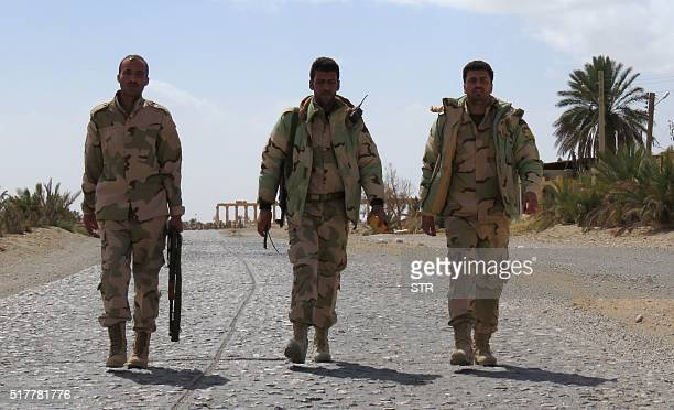 Syrian progovernment forces walk on a street in the ancient city of Palmyra on March 27 after troops recaptured the city from the Islamic State group...