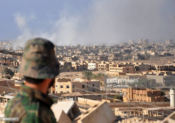 A Syrian progovernment member watches as smoke rises from buildings following an air strike by government forces in the eastern city of Deir Ezzor on...