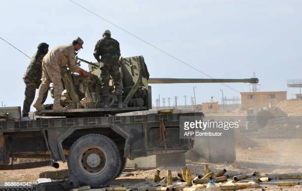 Syrian progovernment members hold a position as they stand on the back of an armoured vehicle in the eastern city of Deir Ezzor on October 31 during...