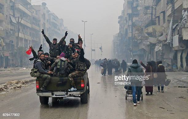 TOPSHOT Syrian proregime fighters gesture as they drive past residents fleeing violence in the restive Bustan alQasr neighbourhood in Aleppo's Fardos...