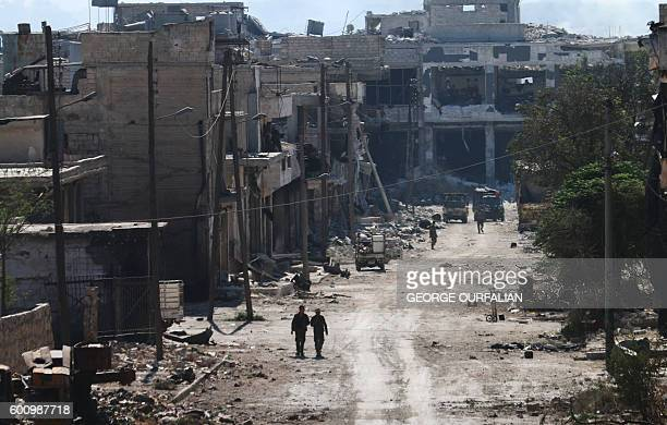 TOPSHOT Syrian proregime fighters walk in a bombedout steet in Ramussa on September 9 after they took control of the strategically important district...