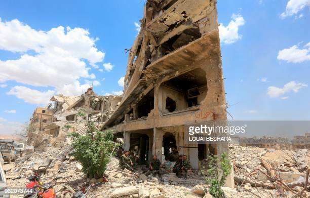 TOPSHOT Syrian proregime forces sit in the shade of a damaged building on Thalateen Street in the Yarmuk Palestinian refugee camp on the southern...