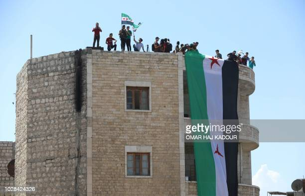 Syrian protesters wave the flag of the opposition as they demonstrate against the regime and its ally Russia in the rebelheld city of Idlib on...