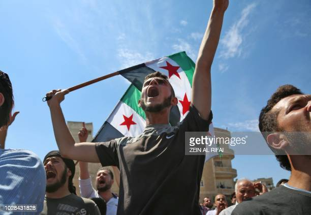TOPSHOT Syrian protesters wave the flag of the opposition as they demonstrate against the regime and its ally Russia in the rebelheld city of Idlib...