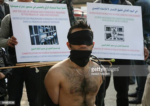 A Syrian protestor mocks being tortured during a sitin to mark International Human Rights Day outside the United Nations offices in downtown Beirut...