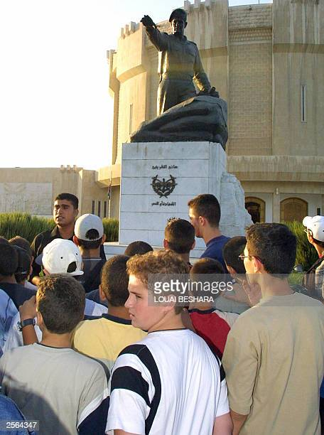 Syrian pupils from the city of Halab listen to their teacher as he stands in front of a statue of the late Syrian President Hafez alAssad at the 06...
