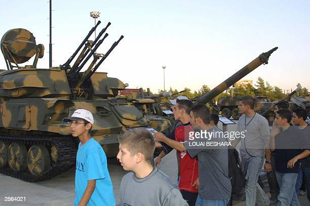 Syrian pupils from the city of Halab walk past a tank similar used in the 1973 ArabIsraeli war at the '06 October Museum' in Damascus 05 October 2003...