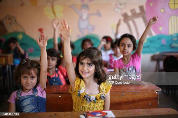 Syrian pupils raises their hands during class in a school in the rebelheld Eastern Ghouta town of Douma on September 18 2017 Syria's sixyear conflict...