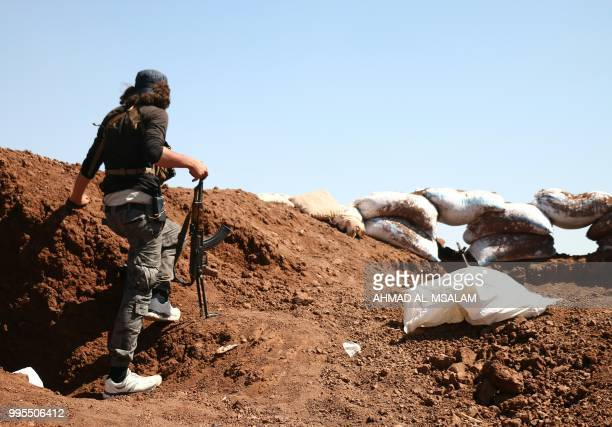 Syrian rebel carries his machinegun during battles with pro-government fighters in western Daraa province on July 10, 2018. - A suicide car bombing...