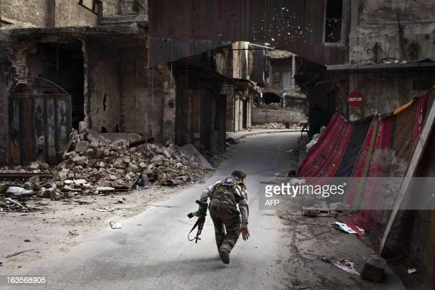 A Syrian rebel crosses a street while trying to dodge sniper fire in the old city of Aleppo in northern Syria on March 11 2013 Syria warned on March...