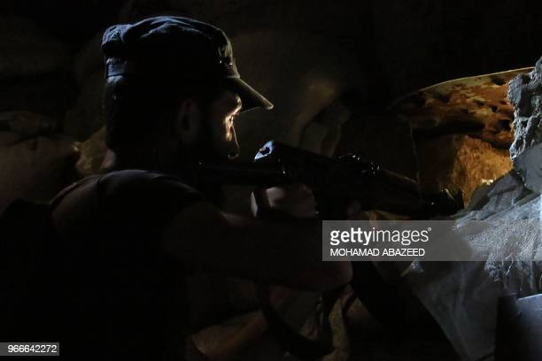 Syrian rebel fighter aims his AK-47 in a fortified area near the frontlines at a rebel-held area in the southern Syrian city of Daraa on June 3, 2018.