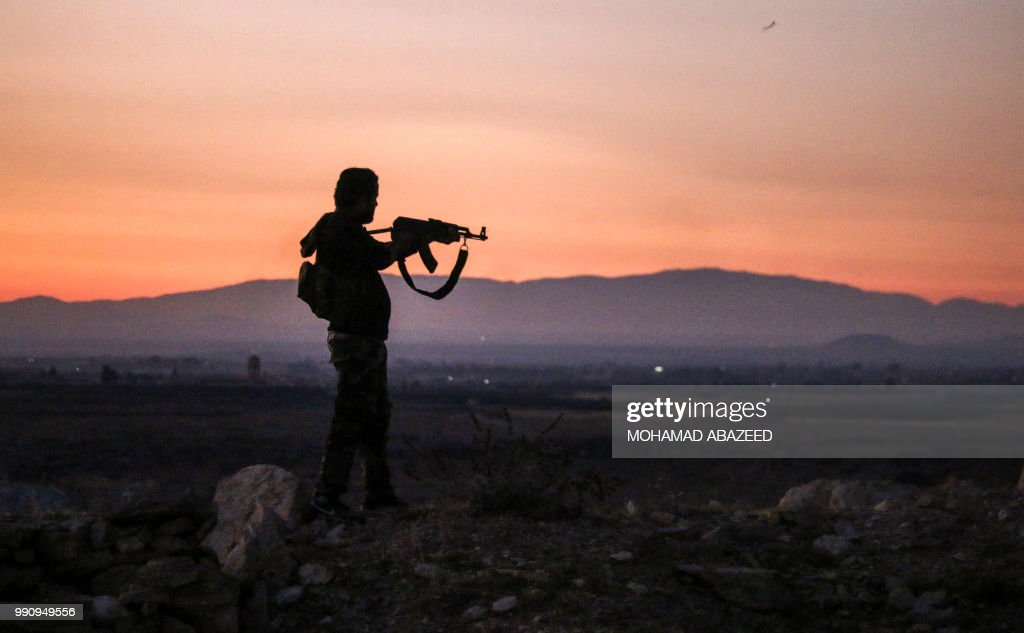 Syrian rebel fighter aims his Kalashnikov assault rifle as he stands near the frontline against government forces west of the embattled southern city of Daraa on July 3, 2018.