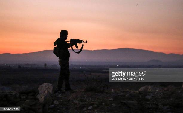 Syrian rebel fighter aims his Kalashnikov assault rifle as he stands near the frontline against government forces west of the embattled southern city...