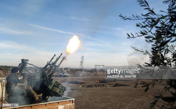 A Syrian rebel fighter belonging to the USbacked Mutasem brigades fires an antiaircraft gun mounted on the back of a pickup truck as he receives...