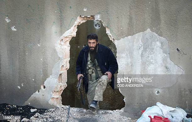 A Syrian rebel fighter emerges from a whole in a wall on the front line in the Aleppo neighbourood of Bustan alBasr on December 8 2012 The rebels...
