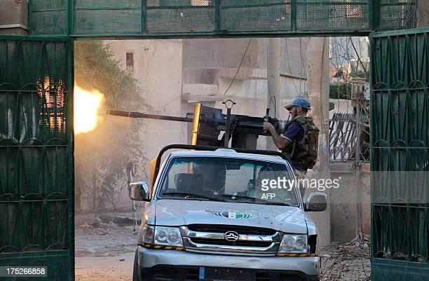 A Syrian rebel fighter fires from a truck during clashes with forces loyal to the regime in the eastern Syrian town of Deir Ezzor on August 1 2013...