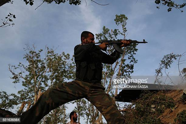 Syrian rebel fighter from the Failaq alRahman aims his weapon on the frontline against regime forces in the rebelcontrolled village of Bala in the...