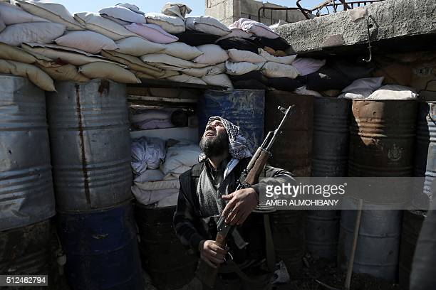A Syrian rebel fighter from the Failaq alRahman brigade mans a position on the frontline against regime forces in the town of Arbin in the eastern...