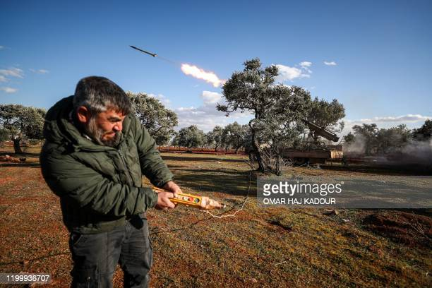 Syrian rebel fighter remotely-fires a rocket from a truck-mounted launcher at a position in the countryside of Idlib towards regime forces positions...