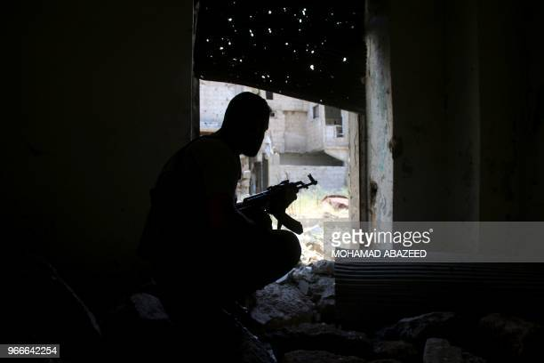 Syrian rebel fighter sits squats as he carries an AK-47 in a fortified area near the frontlines at a rebel-held area in the southern Syrian city of...