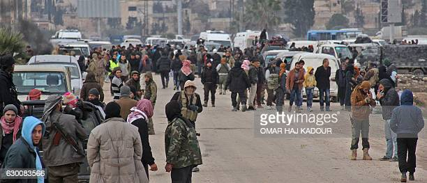Syrian rebel fighters and civilians who were evacuated from rebelheld neighbourhoods in the embattled city of Aleppo arrive in the...