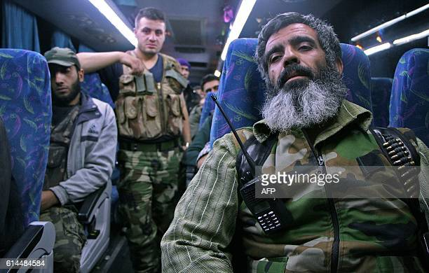 TOPSHOT Syrian rebel fighters and their families arrive on the outskirts of Idlib bordering the Hama province following their evacuation from...