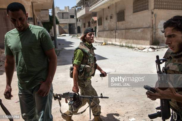 """Syrian rebel fighters belonging to the """"Martyrs of Maaret al-Numan"""" battalion leave their position after a range of shootings on June 13, 2013 in the..."""