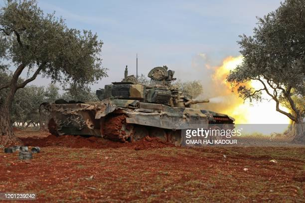 Syrian rebel fighters fire from their position in the countryside of Idlib towards government forces positions, on February 16, 2020.