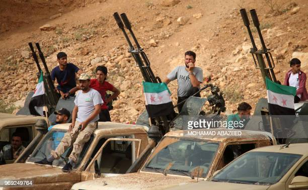 Syrian rebel fighters man antiaircraft guns mounted in the back of pickup trucks during a military parade near the southern city of Daraa on June 7...