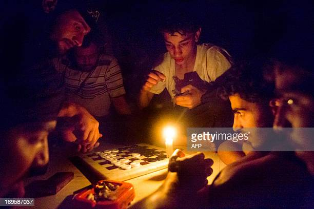 Syrian rebel fighters play a game by candle light due to electricity cuts on May 26 2013 in Adana near the northeastern city of Deir Ezzor Syria's...