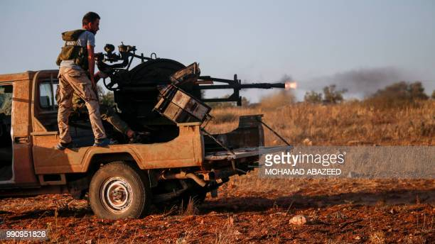 Syrian rebel fighters ride in the back of a pickup truck as one of them fires an antiaircraft gun loaded in the back near the frontline against...