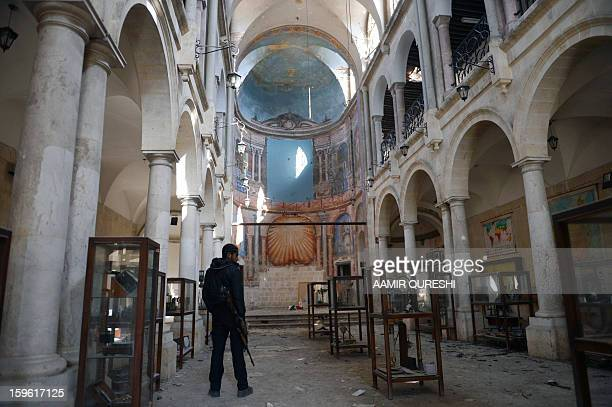 A Syrian rebel looks at damaged display cases inside a former church turned into a film museum which was shelleld by government forces in Aleppo's...