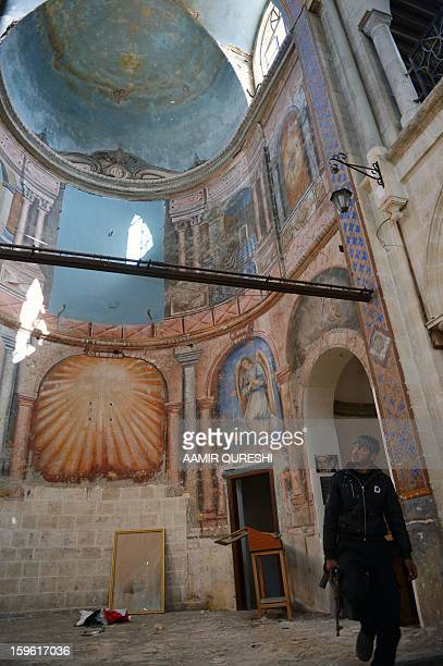A Syrian rebel looks up inside a former church turned into a film museum which was shelleld by government forces in Aleppo's old city on January 17...